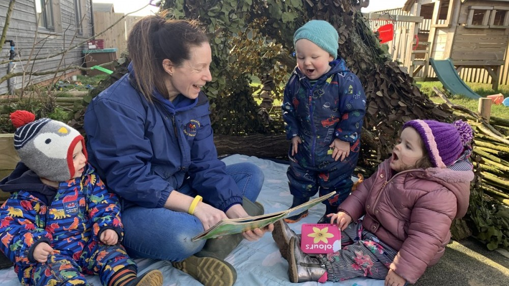 babies reading in garden book den