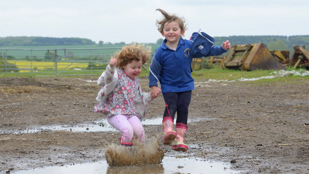 children jumping in muddy puddle in farmyard