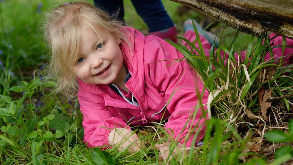child laying in wild grass