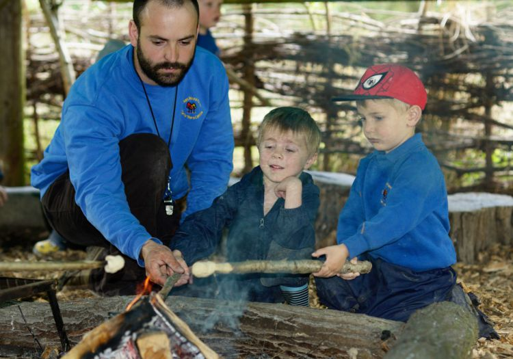 pre-school children toasting marchmallows on forest school