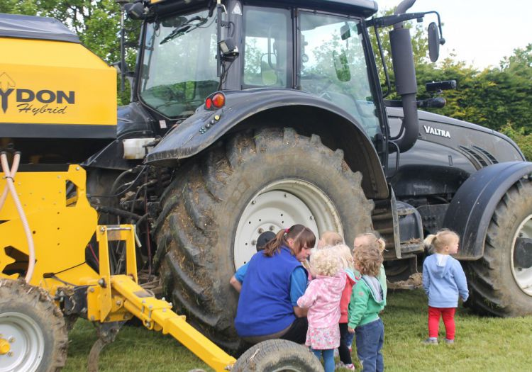 toddlers looking closely at tractor