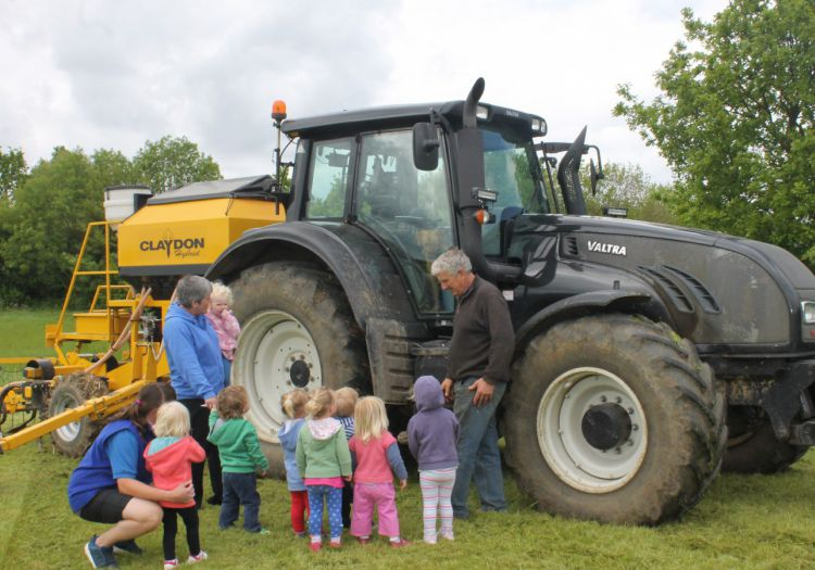 toddlers looking at tractor with farmer