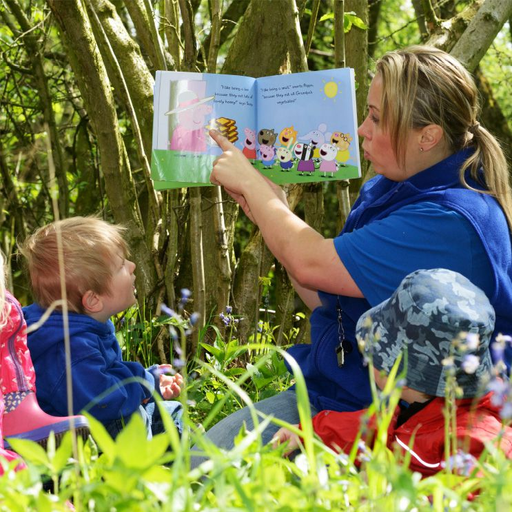 toddlers sharing a story book in woods
